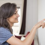 Woman Pushing Thermostat