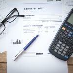 Electric bill with calculator, glasses and a pen